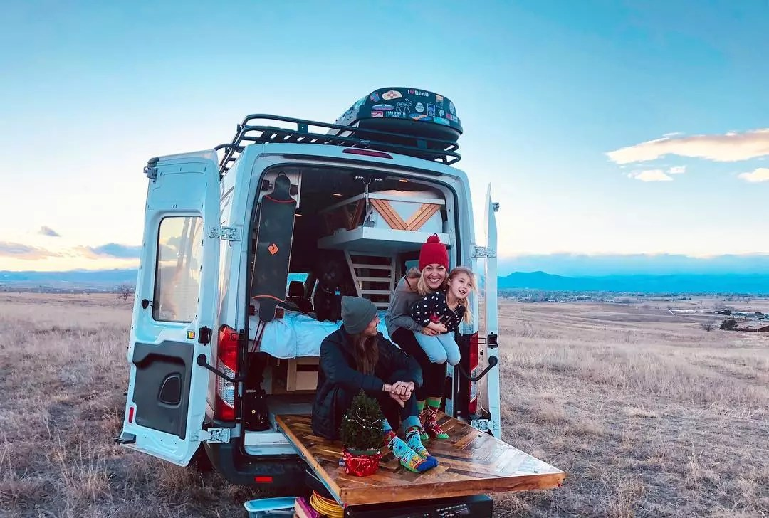 Family sitting on a pullout deck on a van. Photo by Instagram user @fitetravels