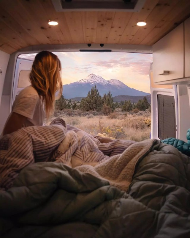 Girl sitting in the back of a van looking at the mountains. Photo by Instagram user @jess.wandering