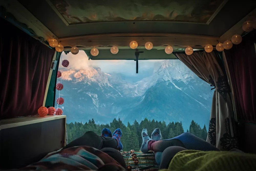 Back of van trunk with string lights by the mountains.