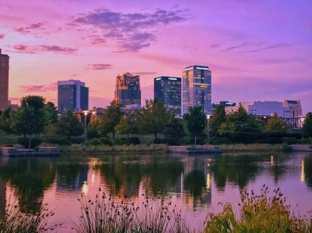 Tall buildings next to water at sunset in Birmingham, AL. Photo by Instagram user @zacksyl