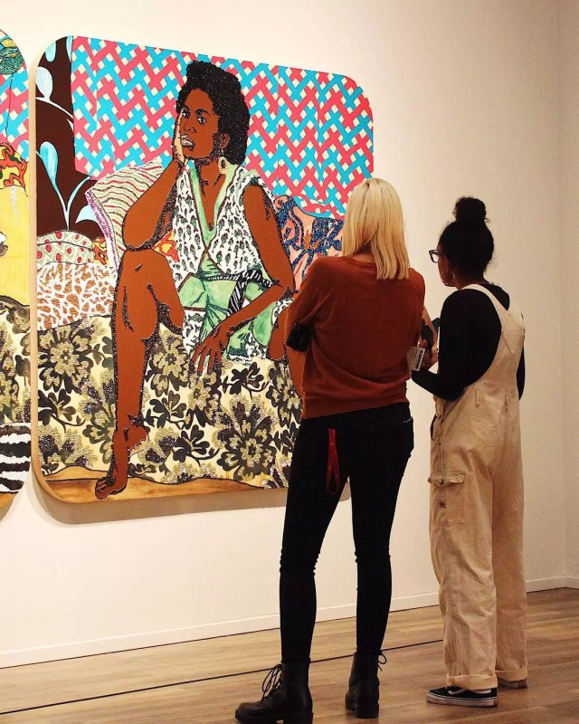 Two women looking at a piece of art of a woman. Photo by Instagram user @tucsonmuseumofart