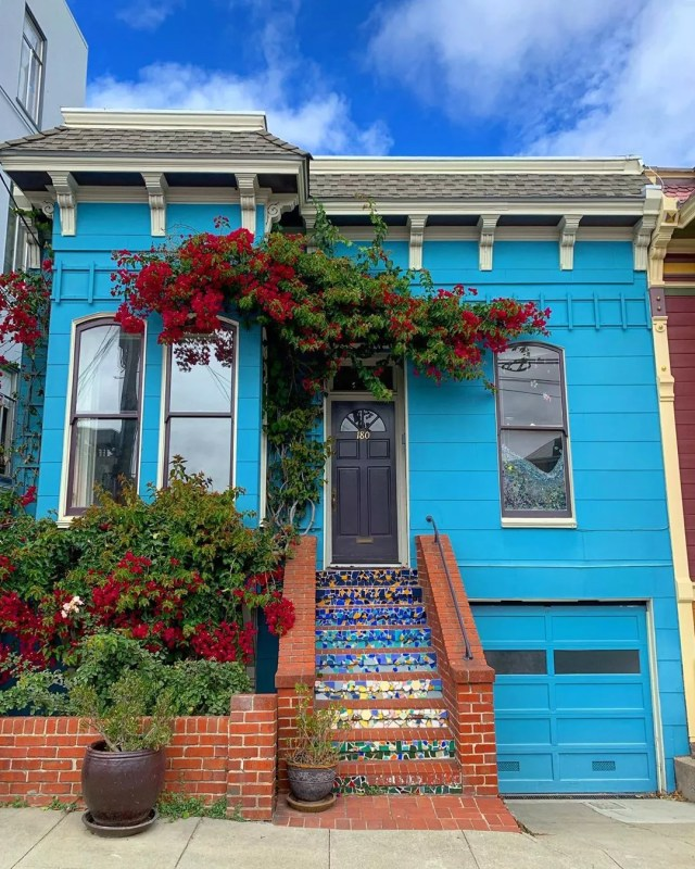 Bright blue house with colorful mosaic steps. Photo by Instagram user @runstagram9