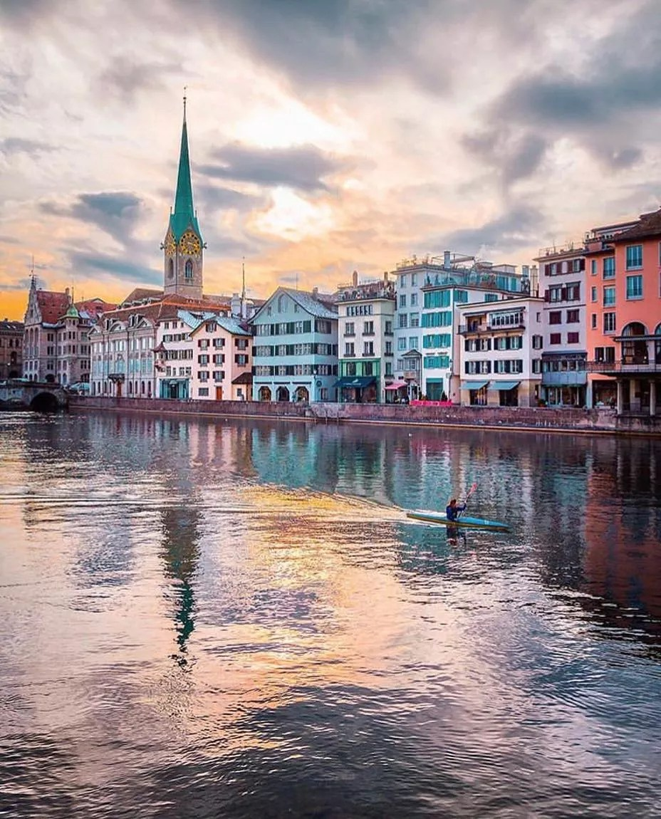 Colorful buildings next to a river in Zurich. Photo by Instagram user @christofs70