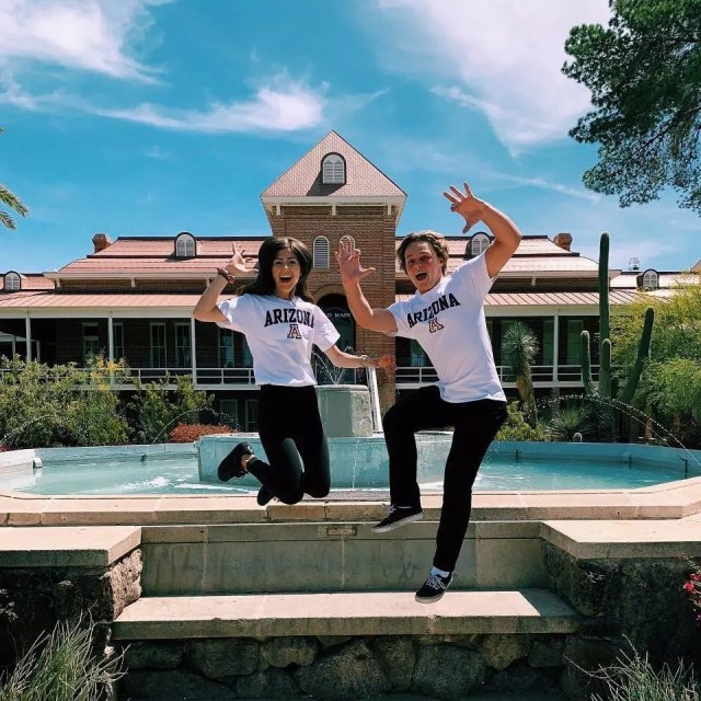 Boy and girl jumping in front of a fountain. Photo by Instagram user @uarizona