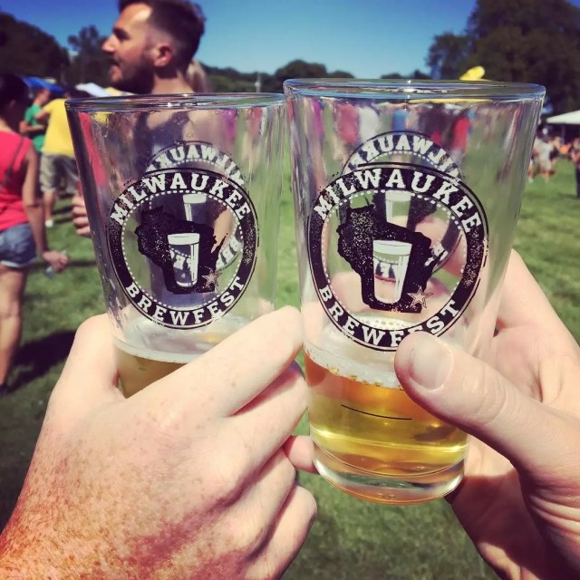 Two people holding up beer glasses at festival. Photo by Instagram user @milwaukeebrewfest