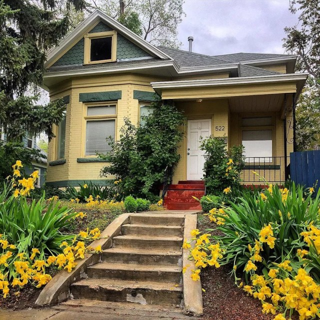 Yellow house with green trim and yellow flowers in the front yard. Photo by Instagram user @lovelyoldhomes