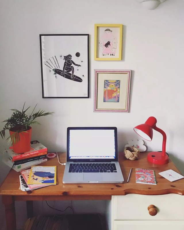Computer on desk and colorful paintings on the wall. Photo by Instagram user @infalmouth