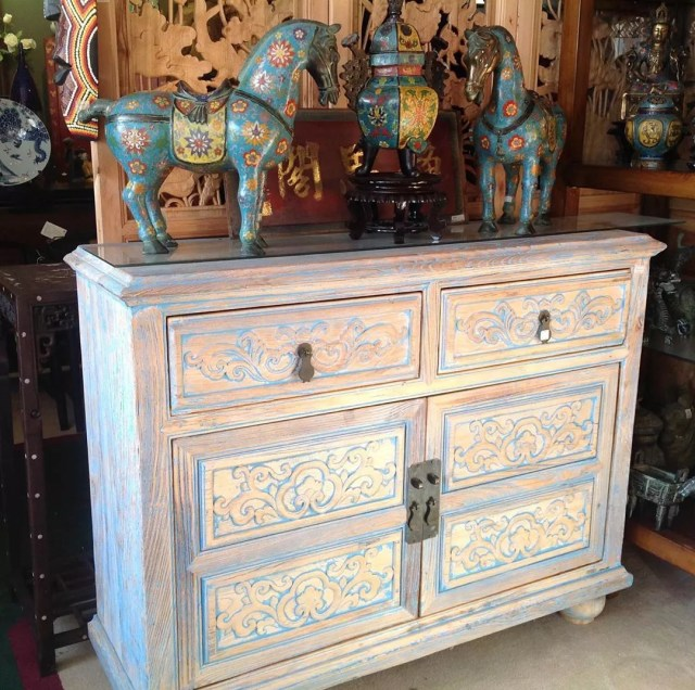 White and blue worn hutch with horse figurines. Photo by Instagram user @goldenlotusinc