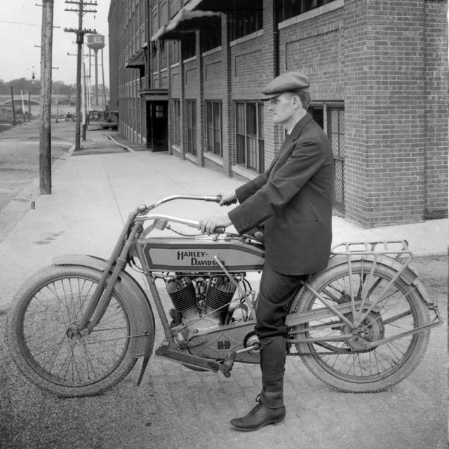 Black and white picture of man riding old motorcycle. Photo by Instagram user @hdmuseum