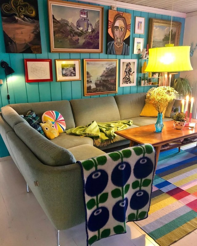 Blue living room with green couch and patterned blanket. Photo by Instagram user @polkadotgrid