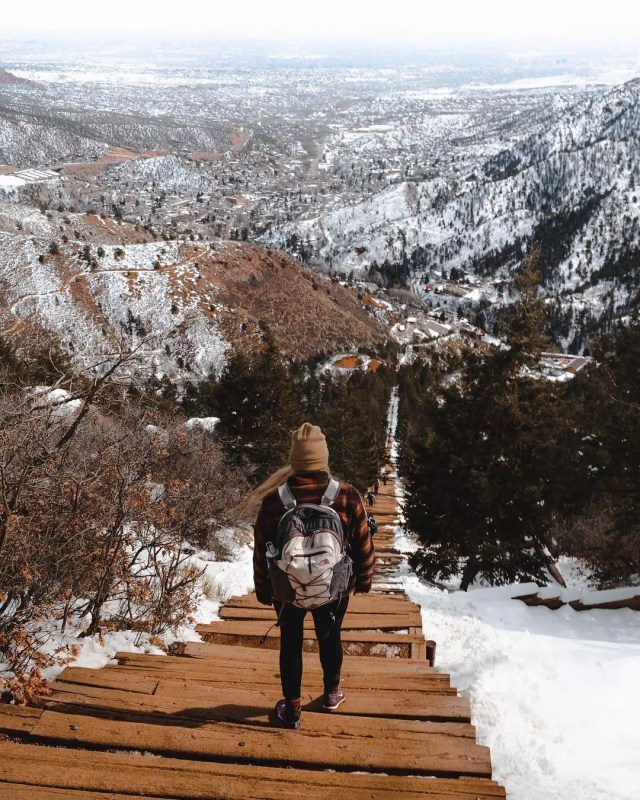 Girl walking down stairs with snowy mountains in the background. Photo by Instagram user @eyethroughmike