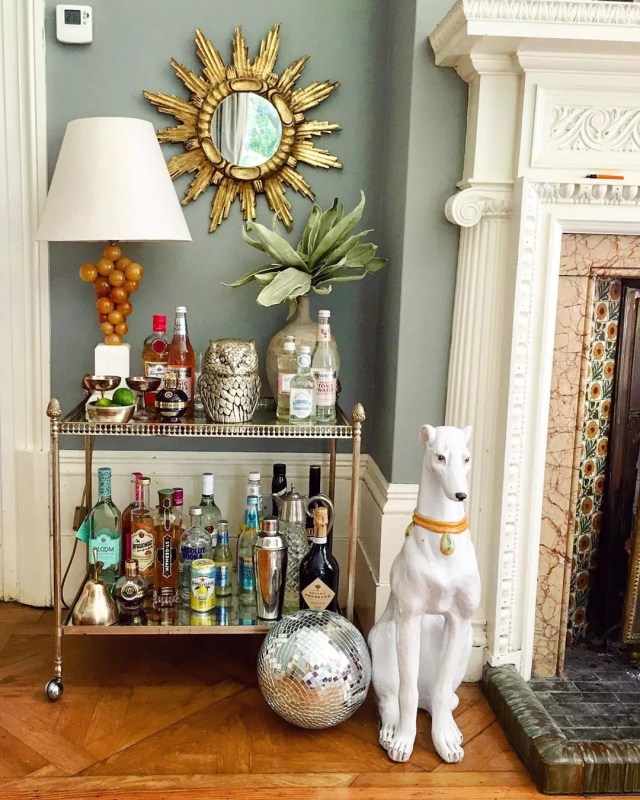 Bar cart with bottles on it and a white dog statue. Photo by Instagram user @thevintagetraderuk
