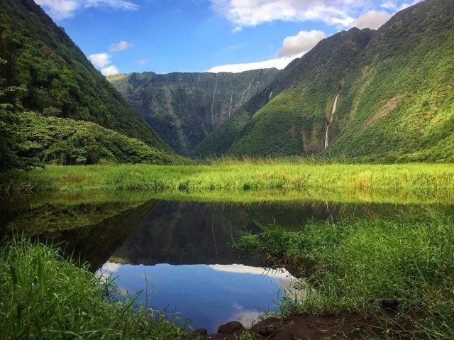 Green valley by water between mountains. Photo by Instagram user @pampuriontherocks