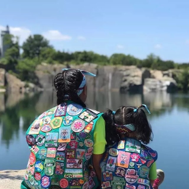 Two girls sitting on a rock wearing girl scouts vests. Photo by Instagram user @girlscouts