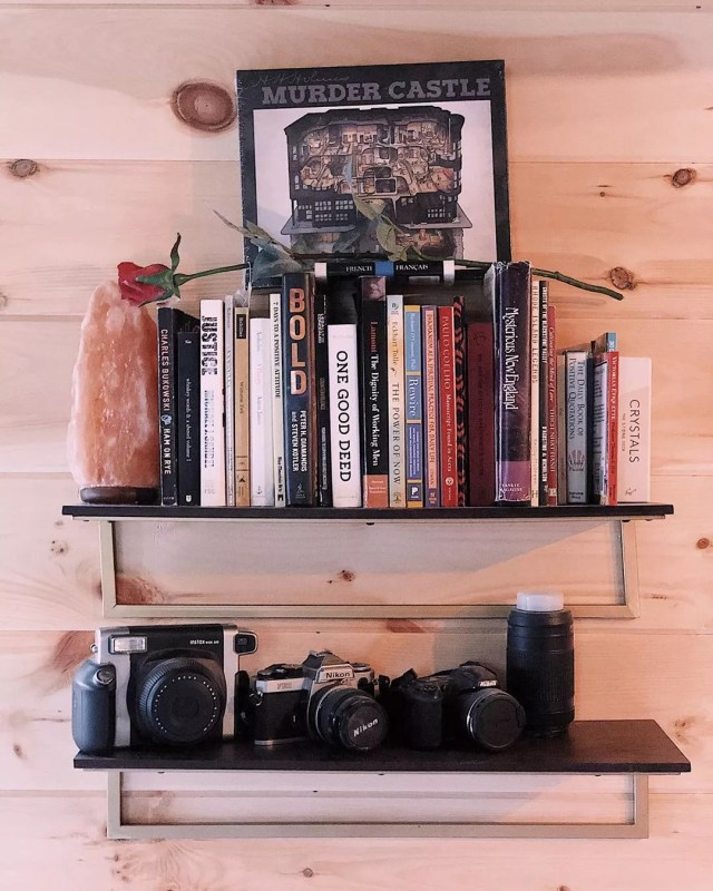 Bookshelf with books, a salt lamp, and cameras on it. Photo by Instagram user @the_tongueandgroovy_tinyhouse