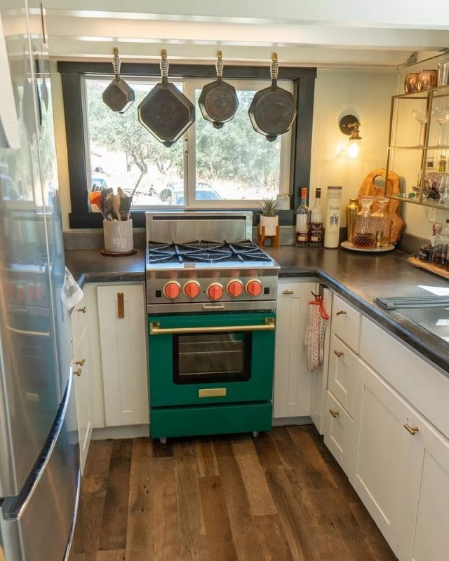 Small kitchen with pans hanging above oven. Photo by Instagram user @tinyhousebasics