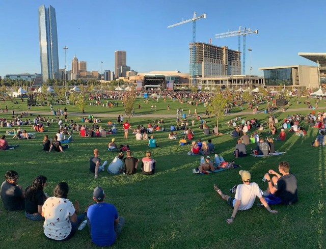 People sitting in a park listening to music. Photo by Instagram user @scissortailpark