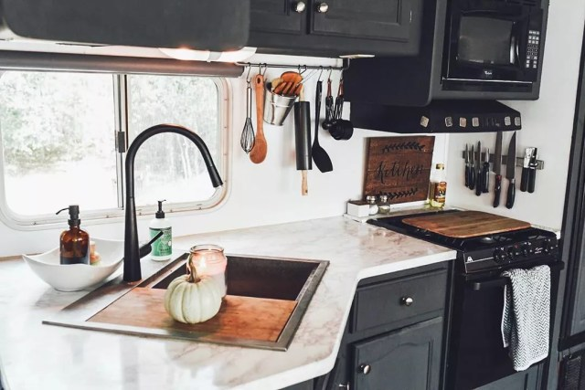 Tiny kitchen with black cabinets and hanging utensils. Photo by Instagram user @leahcboaz