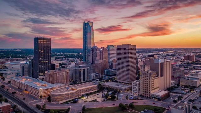 Skyline of tall building with a sun set in OKC. Photo by Instagram user @ericgolda