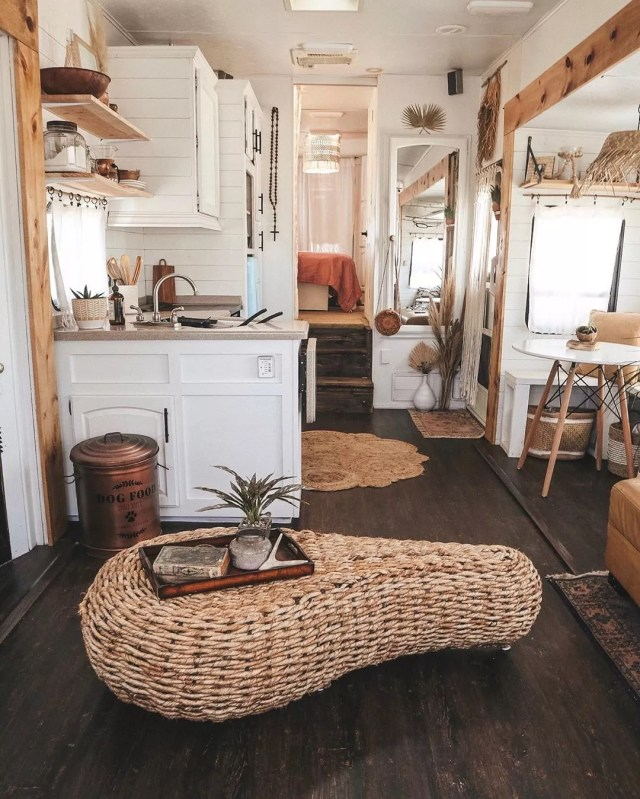 Tiny home with white walls and wicker coffee table. Photo by Instagram user @shelbyadrift