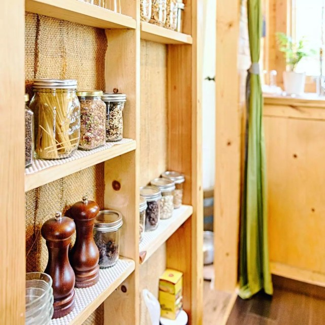 Jars of spices on tiny home support beams. Photo by Instagram user @tinytackhouse