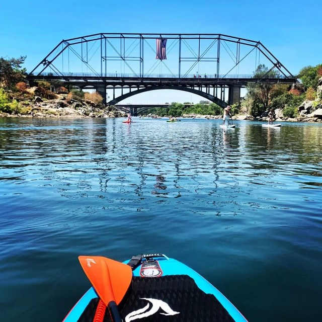 Photo of a Paddleboard Going Under the Rainbow Bridge in Folsom Lake. Photo by Instagram user @lacisauce