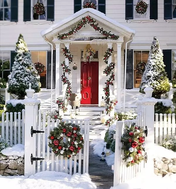 White house with red door covered in Christmas decor. Photo by Instagram user @greencottageideas
