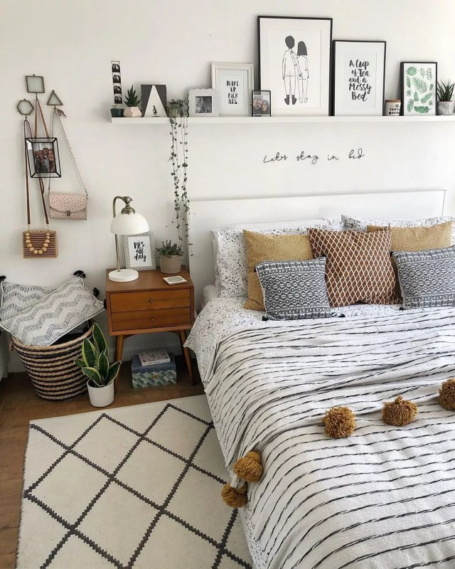 White bedroom with bed adorned in striped sheets and pictures on wall. Photo by Instagram user @nest_number_9