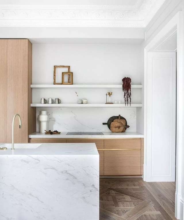 White kitchen with light wood cabinets and marble counters. Photo by Instagram user @banda.property