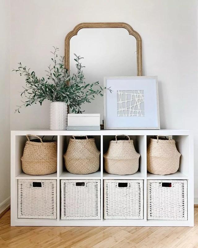 Wicker baskets on white shelf. Photo by Instagram use @simplyciani