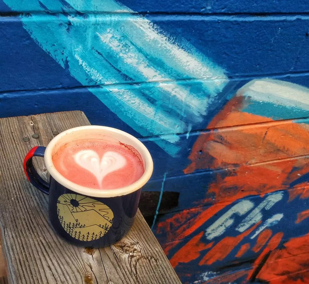 Coffee cup with heart latte art by blue wall. Photo by Instagram user @cosmonautcoffee