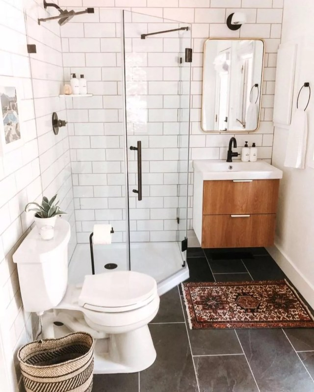Small bathroom with white wall tile and dark floors with glass shower. Photo by Instagram user @kyrosdesigns