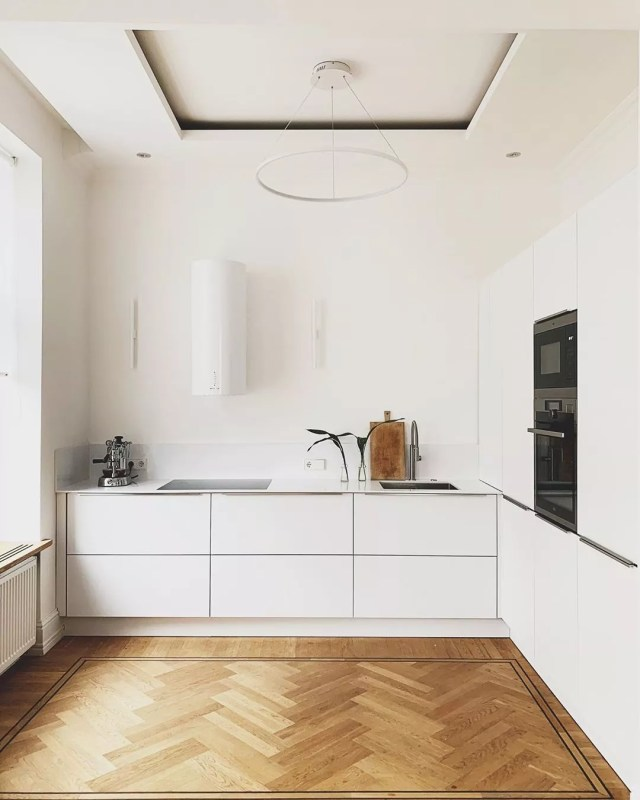 Minimalist kitchen with white walls, white cabinets, and wood floors. Photo by Instagram user @thneu