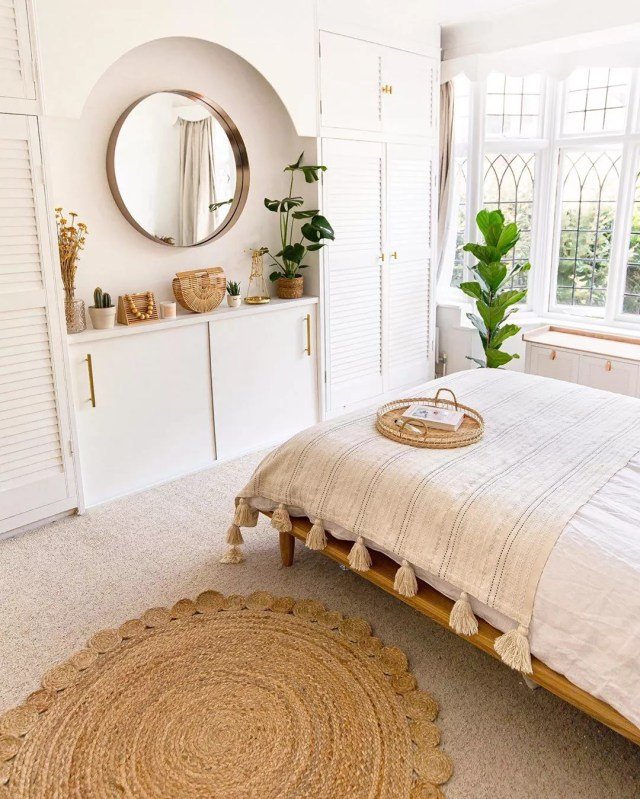White bedroom with white bed and tan rug. Photo by Instagram user @homewithkelsey