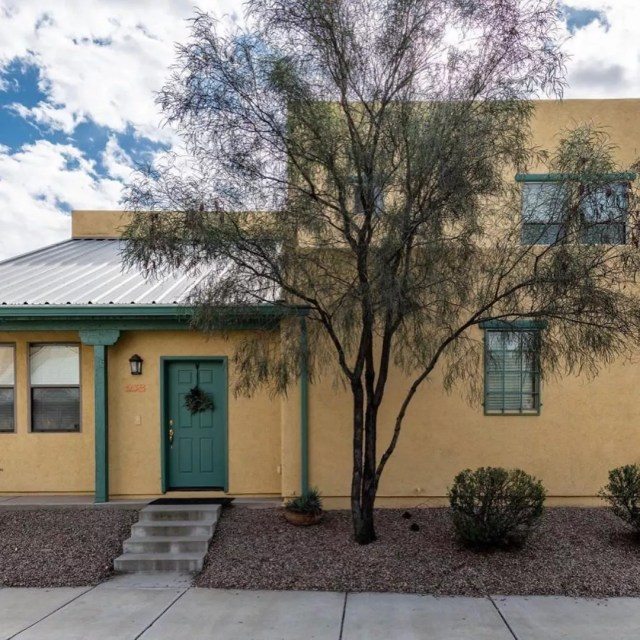 Two story tan house with green door and green trim. Photo by Instagram user @tucsonchoicehomes