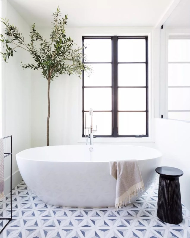 Bathroom with white and tree in corner of room. Photo by Instagram user @amybartiam