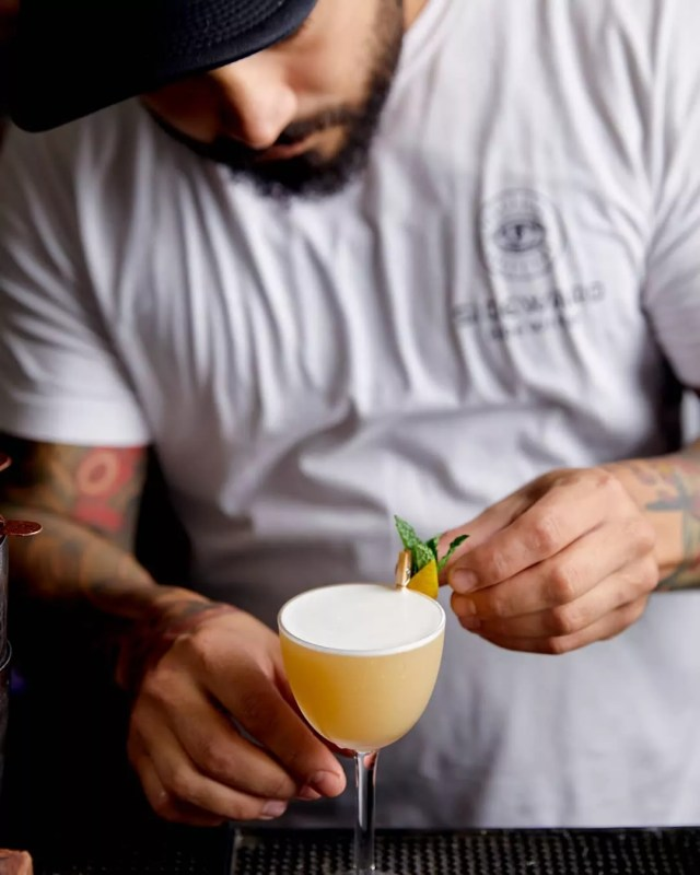 Man pouring cocktail at bar. Photo by Instagram user @thecourtesy