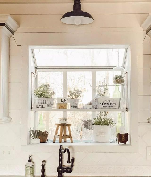 Kitchen window sill holding plants. Photo by Instagram user @rustyrosefarmhouse