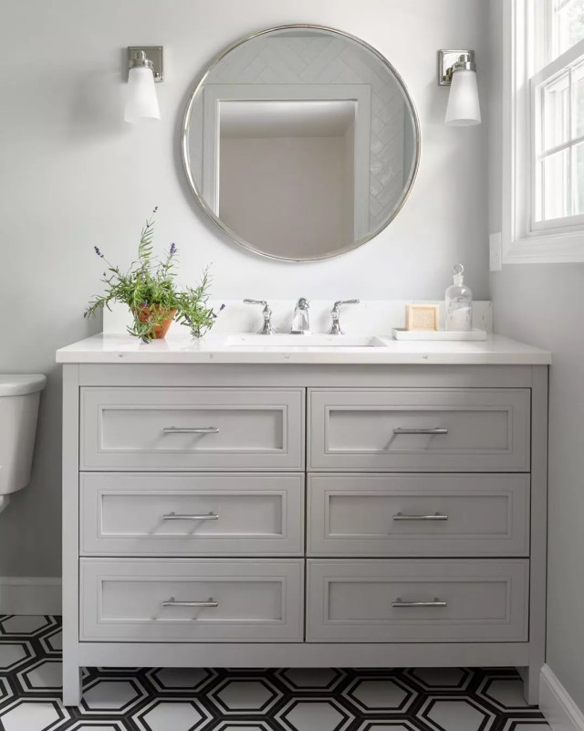 White bathroom with gray cabinets and round mirror above sink. Photo by Instagram user @tamara_flanagan_photo