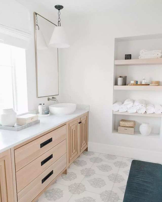 All-white bathroom with blue rug and wood vanity. Photo by Instagram user @kristinabills