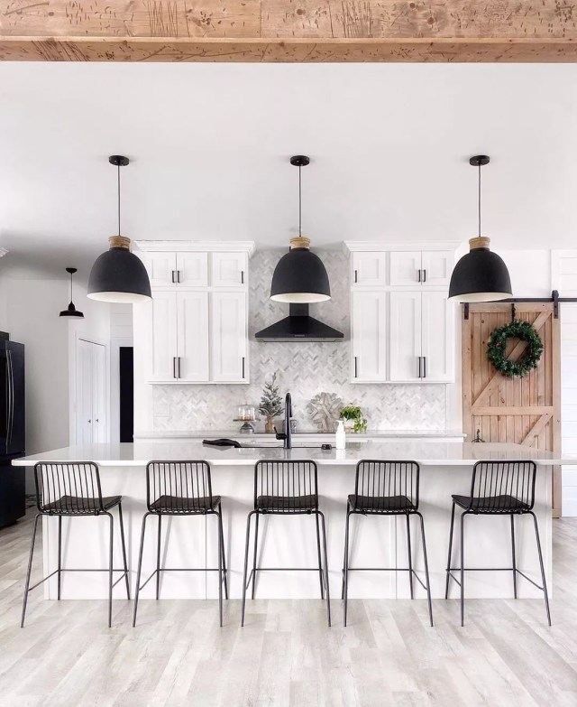 White kitchen with white cabinets and black light fixtures. Photo by Instagram user @fournorthfarmhouse