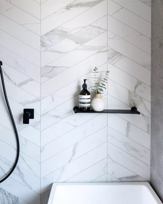 Marble tile bathroom with black floating shelf about tub. Photo by Instagram user @hatchrenovations