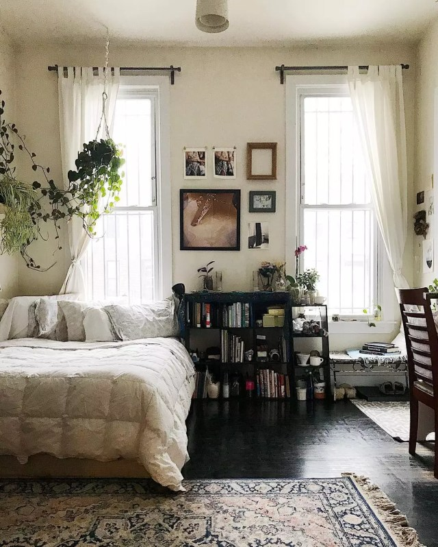 All white bedroom with dark floors in apartment. Photo by Instagram user @etshipley