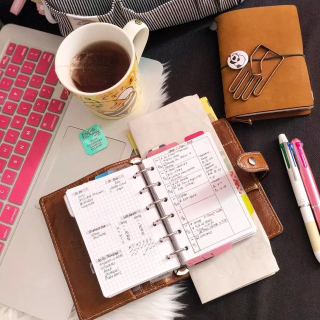 Planner and cup of coffee by laptop. Photo by Instagram user @blissful_pages