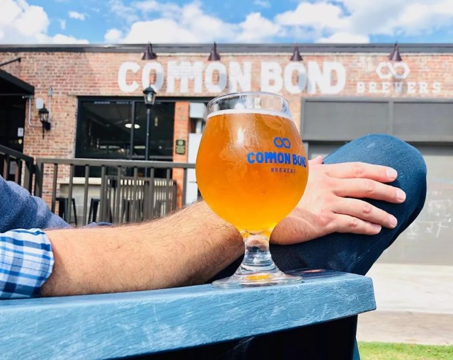 Beer glass on arm on chair. Photo by Instagram user @commonbondbrewers
