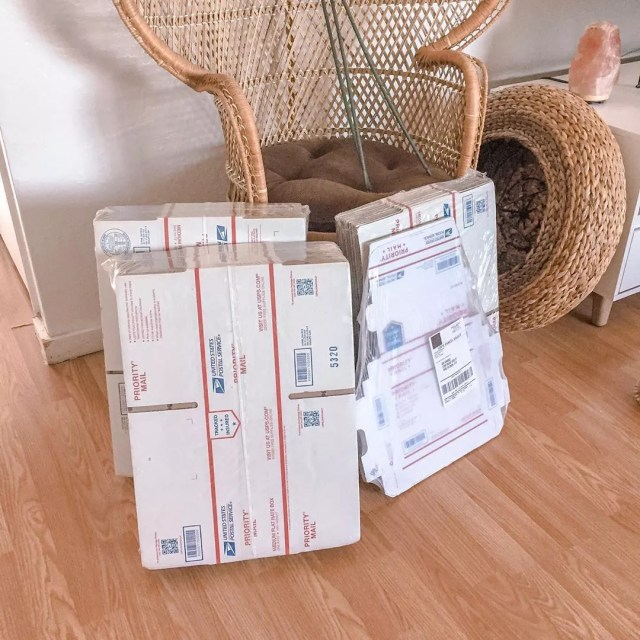 Packs of USPS boxes by chair. Photo by Instagram user @h0llaaaaaa