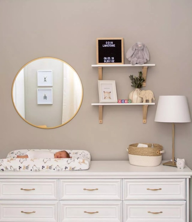 white dresser used as a baby changing table with mirror on wall photo by Instagram user @reneeannelavictoire