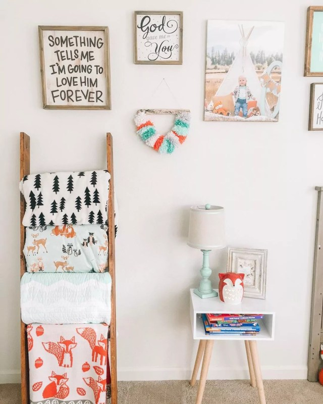 ladder with blankets stored on rungs and photos on white wall photo by Instagram user @oak.and.co