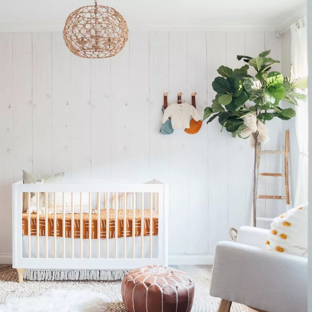 White nursery with orange crib. Photo by Instagram user @readysetrico