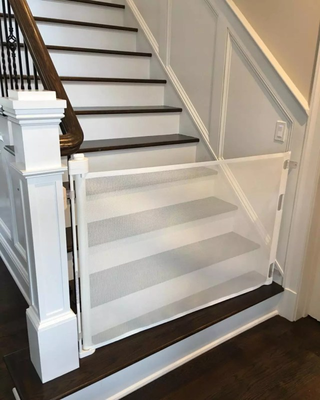 Baby gate blocking stairs. Photo by Instagram user @pbandjbabyproofing_playrooms